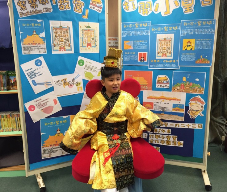"<p>A student dressing up as an emperor was promoting the educational activity, ""Mali Mali Palace"", in front of a bulletin board with many promotional materials designed by the teachers on it.</p>"